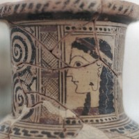 Head girls painted on throat late archaic island vase. Ear drop in left ear is embedded also in face. Left is decorated double spiral 200x200 Ancient Swastika
