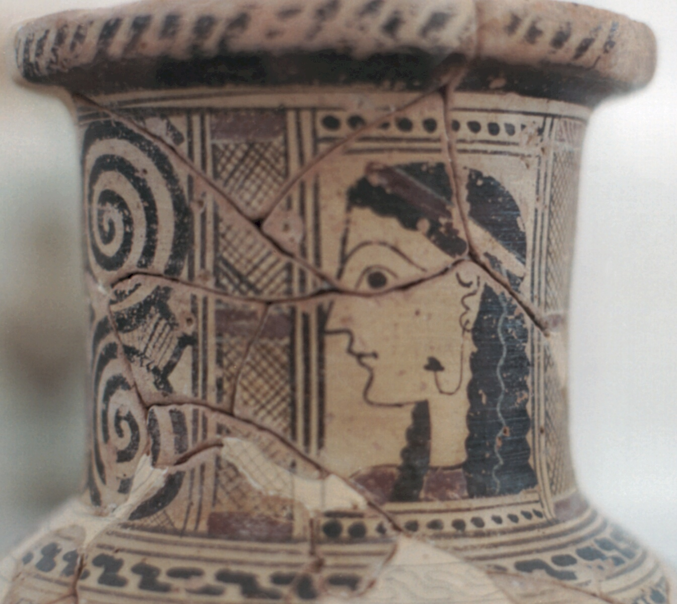 Head girls painted on throat late archaic island vase. Ear-drop in left ear is embedded also in face. Left is decorated double spiral